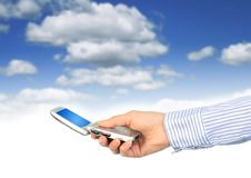 Cell phone in hand. Over blue sky background Stock Photography