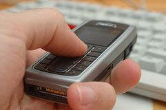Cell phone in a hand. Cell phone Nokia in males hand with white keyboard on background Royalty Free Stock Photos