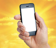 Cell Phone Hand Sky. A cell phone being with a blank white screen and a sky background Royalty Free Stock Photography