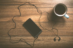 Cell phone with headphones and coffee on wood Royalty Free Stock Photography