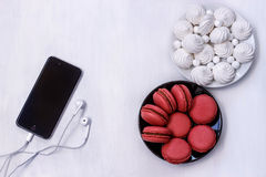 Cell phone with headphones, macaroons and meringues on white table. Black cell phone with white headphones, macaroons and meringues on white table Stock Image