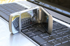 Cell phone on the keyboard Stock Photo