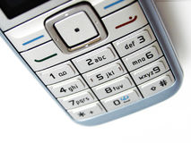 Cell Phone Keypad. Alpha-Numeric keypad of cell phone with black numbers and letters on silver keys.  Blue phone case and other navigational keys are visible Royalty Free Stock Photography