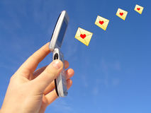 Cell Phone Love Messages. Hand holding an open cell phone with illustrations of envelopes sealed with red hearts emanating from the phone.  Isolated on blue sky Stock Photo