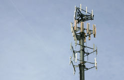 Cell Phone / Microwave tower. Cluster of cell phone & microwave receiver / transmitters at the top of a single column steel tower. Shot is horizontal with a stock images