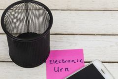 Cell phone near trash can with the words: Electronic Urn.  stock image