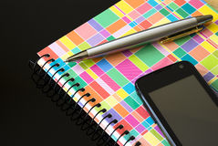 Cell phone with notebook and ballpoint. Black cell phone with colorful notebook and silver pen isolated on black background Royalty Free Stock Photos