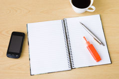 Cell phone, notebook and cup of coffee. Cell phone with spiral notebook and cup of coffee arranged on office table Royalty Free Stock Photos
