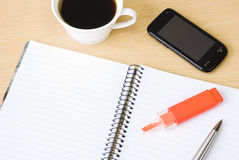 Cell phone, notebook and cup of coffee. Cell phone with spiral notebook and cup of coffee arranged on office table Royalty Free Stock Photography