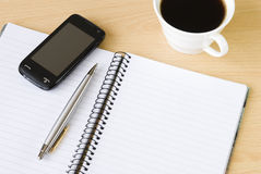 Cell phone, notebook and cup of coffee. Cell phone with spiral notebook and cup of coffee arranged on office table Stock Image