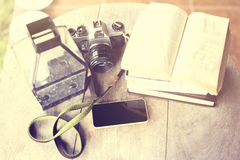 Cell phone, old camera and books on a wooden table Royalty Free Stock Photo