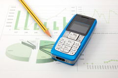 Cell phone over business chart Royalty Free Stock Photos