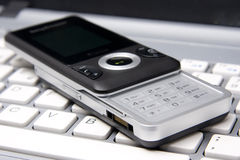 Cell phone over laptop Stock Images