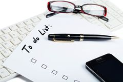 Cell phone, pen and glasses on top of a to do list royalty free stock image