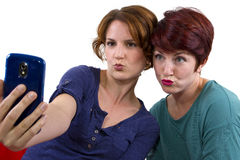 Cell Phone Pics. Two women taking self portraits with a cell phone stock photos