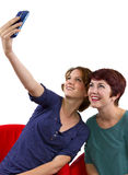 Cell Phone Pics. Two women taking self portraits with a cell phone stock photography