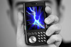 Cell Phone Radiation. A man holds a cell phone with a lightning bolt illustration on the screen. Great image to illustrate cell phone radiation royalty free stock images