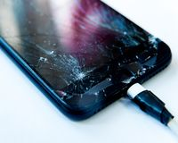Cell phone with the screen broken by a hammer. non-warranty repairs concept.  royalty free stock photos