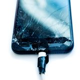 Cell phone with the screen broken by a hammer. non-warranty repairs concept.  stock image