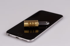 Cell phone security - lock and phone on white Royalty Free Stock Photos
