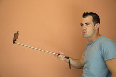 Cell phone selfie extender and silly male model Royalty Free Stock Images
