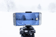 Cell Phone Shooting Video In Freezing Cold. Image showing a cell phone being used to shoot video in extreme cold and wet weather stock image