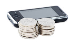Cell phone and stacks of coins Stock Image