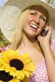 Cell Phone and Sunflowers. A beautiful young blond woman carrying a basket of sunflowers and talking on her mobile phone Stock Images