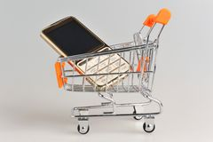 Cell phone in supermarket pushcart on gray background Stock Photography