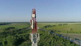 Cell phone telecommunication tower, drone view of worker servicing antenna stock video footage