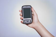 Touchscreen mobile device. Cell phone with touchscreen in female hand on gray background Stock Photos