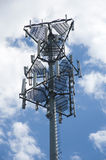 Cell phone tower. Against blue sky with scattered clouds Royalty Free Stock Images