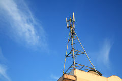 Cell Phone Tower on building against blue sky Stock Image