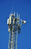 Cell phone tower over blue sky Royalty Free Stock Photos