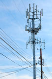 Cell  phone tower rises against a blue sky Stock Photography