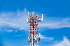 Cell phone tower rises against a blue sky. Stock Photo
