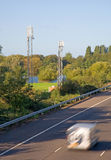 Cell Phone Towers by a Motorway. Cell phone antenna towers used for GSM and 3G by a motorway (M3) in the UK near Shepperton royalty free stock photos