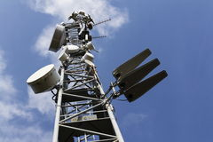 Cell phone transmitters on telecommunication tower on sunny day Stock Photos