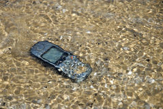 Cell-Phone under water. Mobile-Phone on the beach is now under water stock image