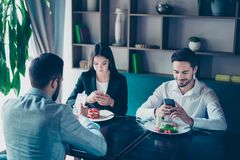 Cell phones addiction. New generation, busy people, lunch and me. Eting in a restaurant, wearing formal clothes, having nice tasty food royalty free stock image