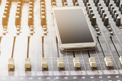 Cell phones. On the audio mixer in the Control Room Stock Images