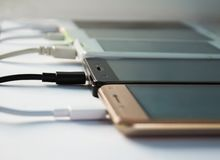 Cell phones on desk, connected to charger. Lot of smart phones on white background charging with cables stock image