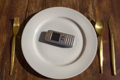 Cell on plate. Cell phone placed on plate with golden cutlery next to it. Consumerism concept Stock Images