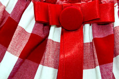 Cell textile texture. White and red cell textile texture with a red button and a bow on it royalty free stock images