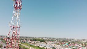 Cell Tower. City communications. Aerial shoot. Cell tower in red and white. City communications. Summer time. Aerial filming stock footage