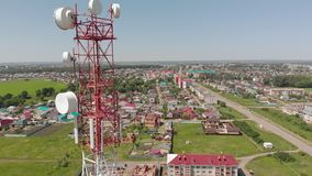 Cell Tower. City communications. Aerial shoot. Cell tower in red and white. City communications. Summer time. Aerial filming stock video footage