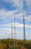 Cell towers on the mountain. Cell towers in the colorful trees with a view of mountains behind them stock photos
