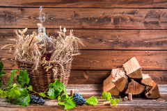 Cellar with demijohn of red wine. On old wooden table Royalty Free Stock Images