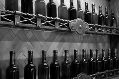 Cellar shelves with dark corked wine bottles against wooden wall black and white monochrome. Shelves with dark corked full wine bottles and forged items against Stock Image