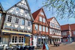 Celle, Alemanha - 1º de maio de 2017: Povos que descansam na rua com a fachada da construção no Celle Cidade velha em Alemanha Foto de Stock